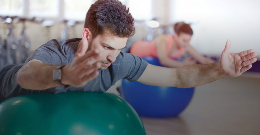 Couple training in fitness studio on gym balls